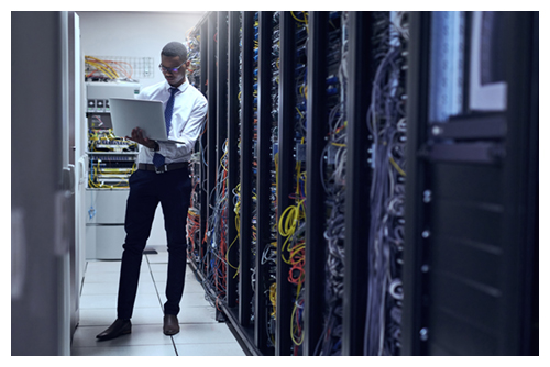 Cropped shot of a IT technician working on his laptop while standing inside of a server room